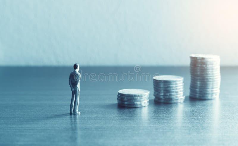 La gente miniatura che sta con lo sguardo della pila conia circa il financia fotografie stock