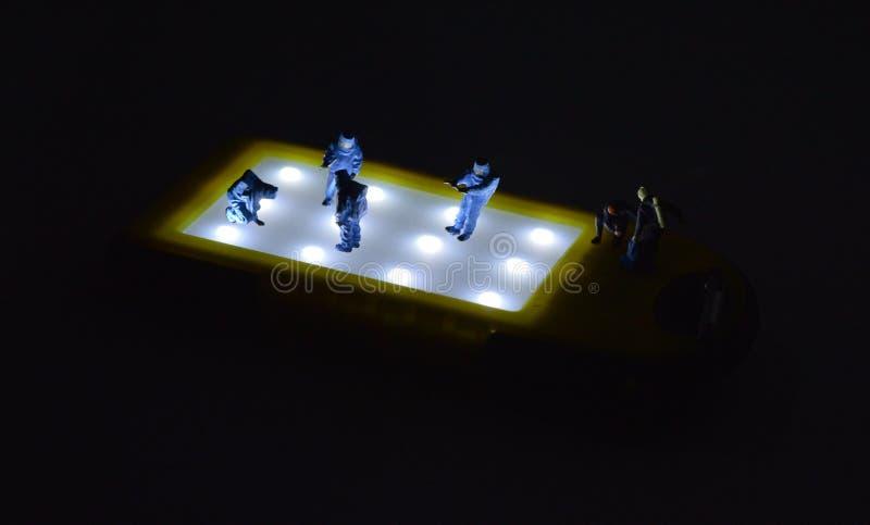 La gente miniatura en trajes del hazmat está trabajando con el fondo negro foto de archivo libre de regalías