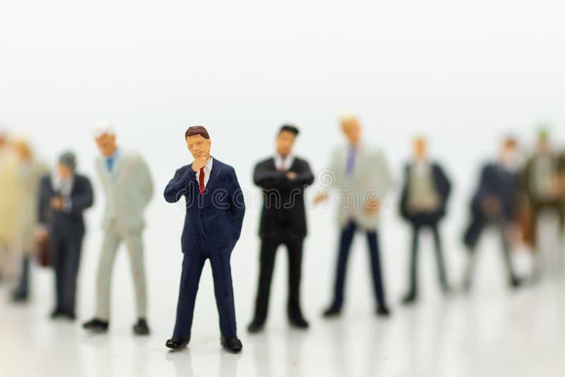 La gente miniatura, grupo de hombres de negocios trabaja con el equipo, usando como opción del fondo del empleado más adecuado, imágenes de archivo libres de regalías