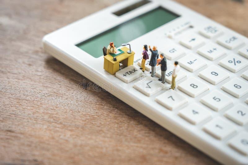 La gente miniatura paga el IMPUESTO de los ingresos anuales de la cola por el a?o en la calculadora el usar como concepto y finan fotos de archivo