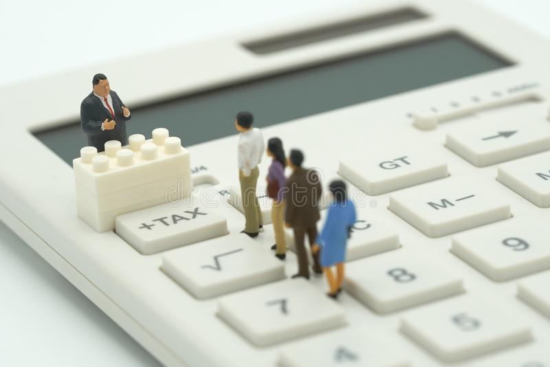 La gente miniatura paga la TASSA di reddito annuo della coda l'anno sul calcolatore usando come il concetto di affari del fondo e fotografie stock libere da diritti