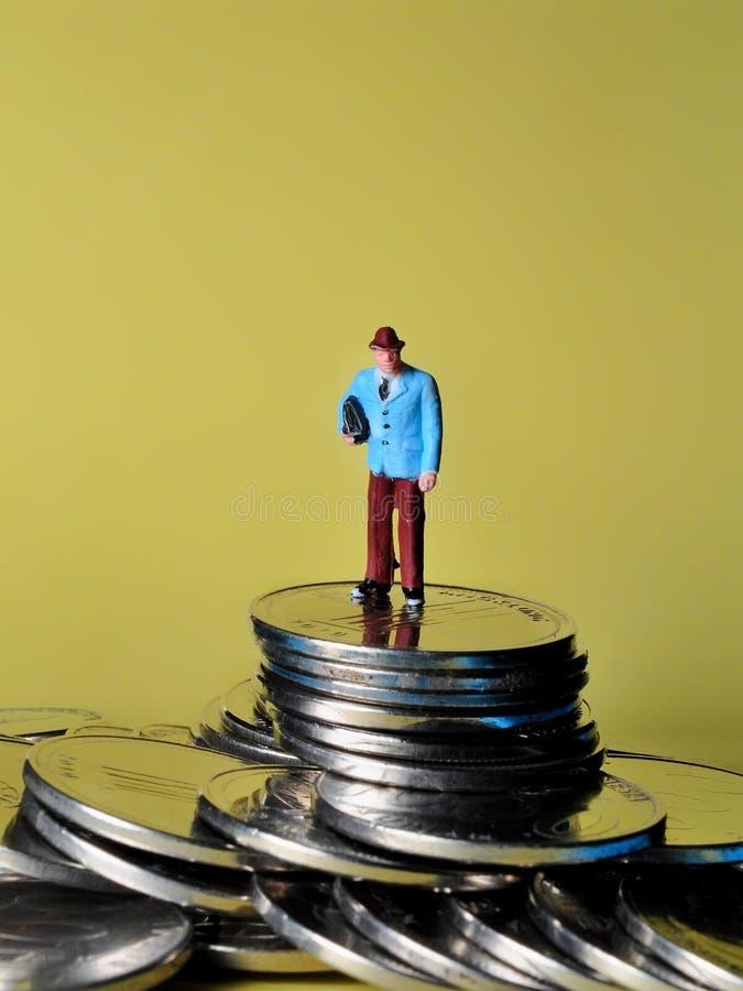 La gente miniatura que se sienta en la parte superior de la pila de monedas disfruta de su renta o la gana imagenes de archivo