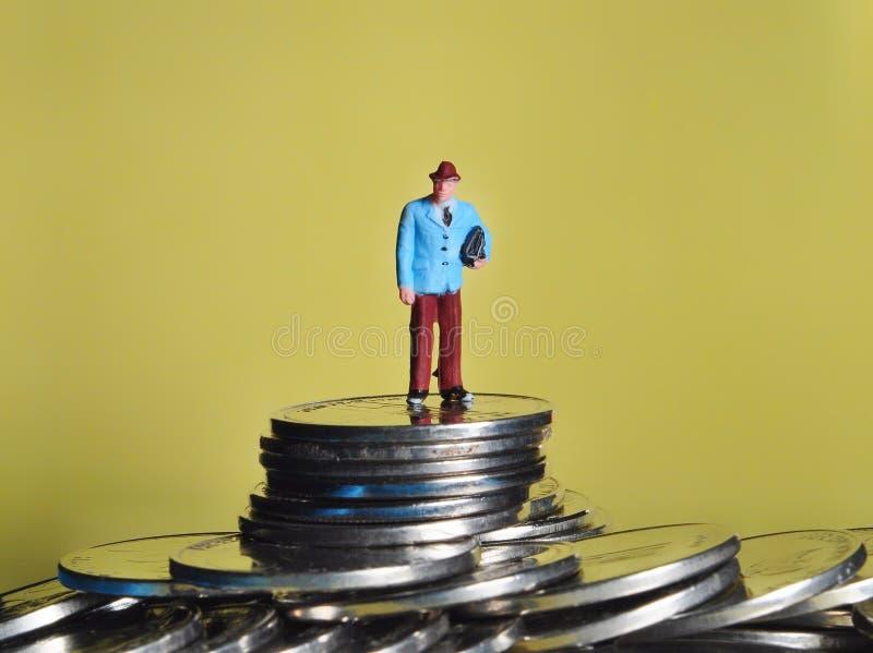 La gente miniatura que se sienta en la parte superior de la pila de monedas disfruta de su renta o la gana fotos de archivo