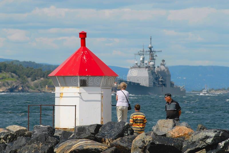 La gente mira a militares enviar el paso por el fiordo en Frogn, Noruega foto de archivo