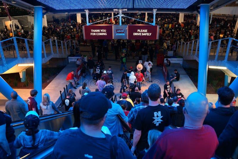 La gente monta abajo de la escalera móvil hacia el estacionamiento t del transporte público y imagen de archivo