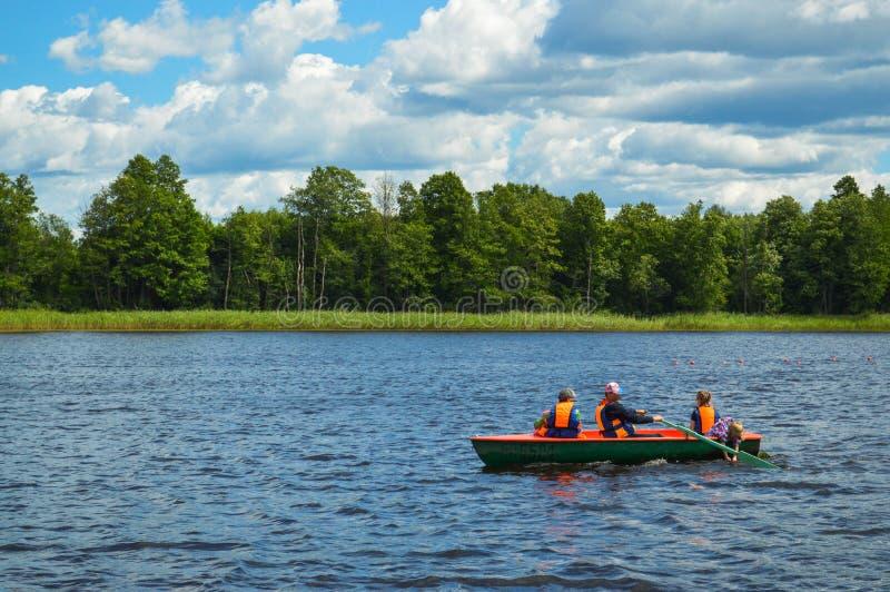 La gente monta en un viaje del resto de la lancha de carreras del barco en el agua en el fondo de la naturaleza hermosa del lago  imagen de archivo
