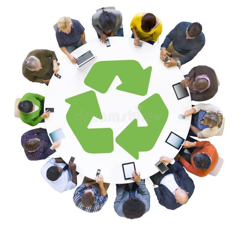 La gente multietnica che per mezzo dei dispositivi di Digital con ricicla il simbolo illustrazione di stock