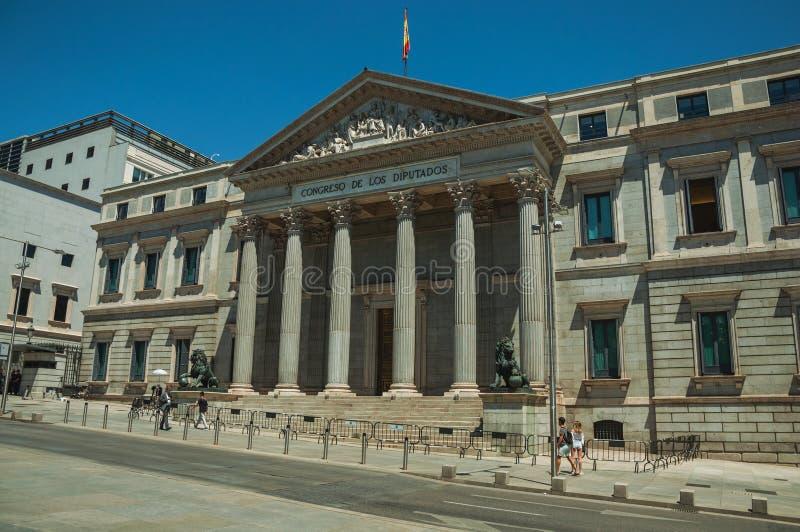 La gente nella parte anteriore la facciata dei las Cortes di Palacio de a Madrid immagine stock
