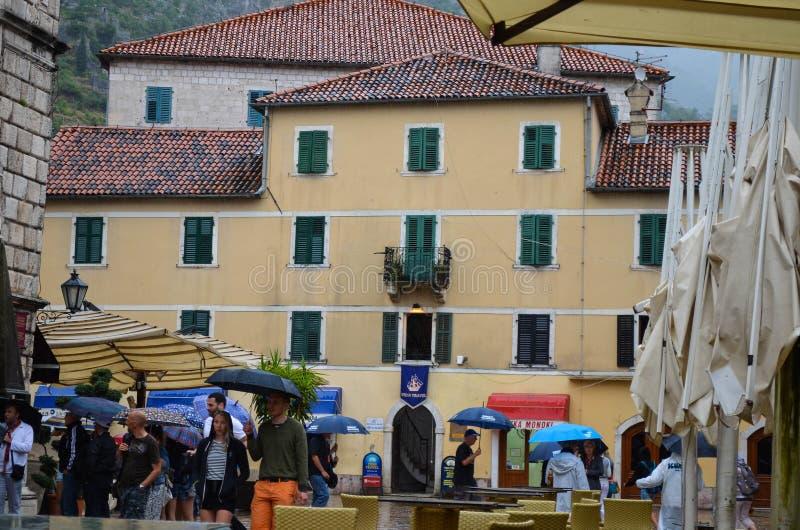 La gente nella pioggia nel quadrato in Cattaro, Montenegro immagini stock libere da diritti