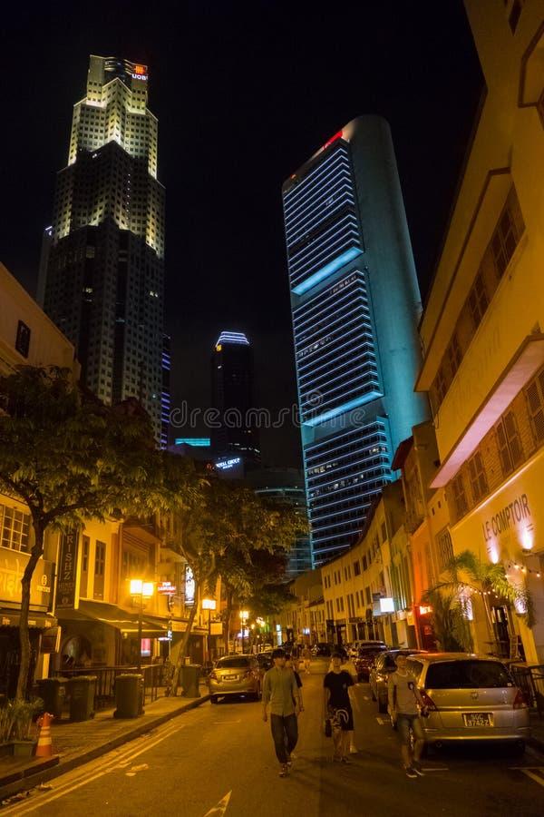 La gente nella via ed alte costruzioni dei grattacieli a Singapore alla notte immagine stock
