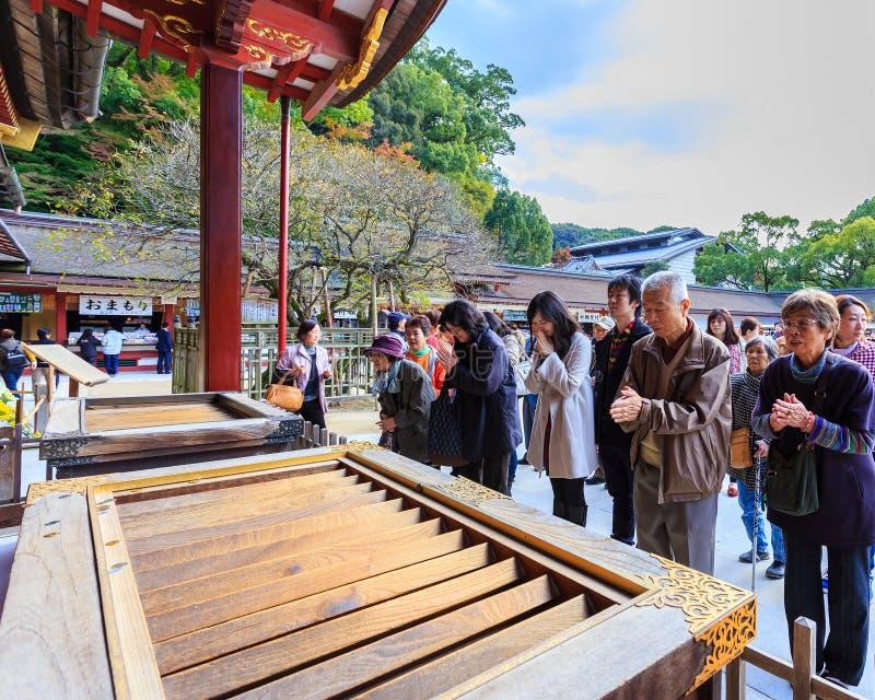 La gente no identificada ruega delante de Dazaifu Tenmangu foto de archivo