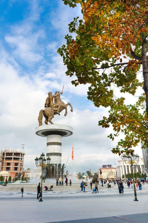 La gente non identificata cammina attraverso il quadrato della Macedonia sotto il guerriero su un monumento del cavallo di Skopje immagini stock libere da diritti