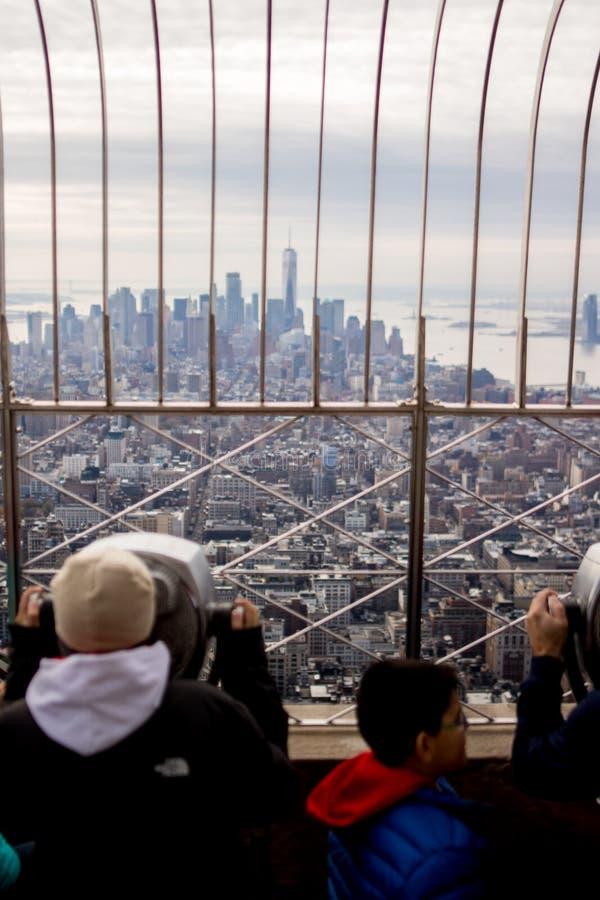 La gente osservando l'orizzonte di New York dalla piattaforma di osservazione dell'Empire State Building immagini stock libere da diritti