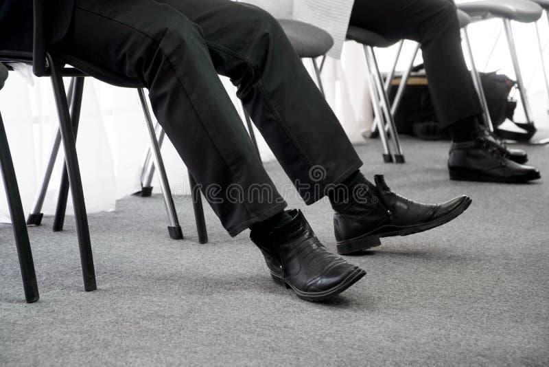 La gente parada espera su vuelta una entrevista, sentándose en sillas de la oficina en el vestíbulo Búsqueda del desempleo y de t imagenes de archivo