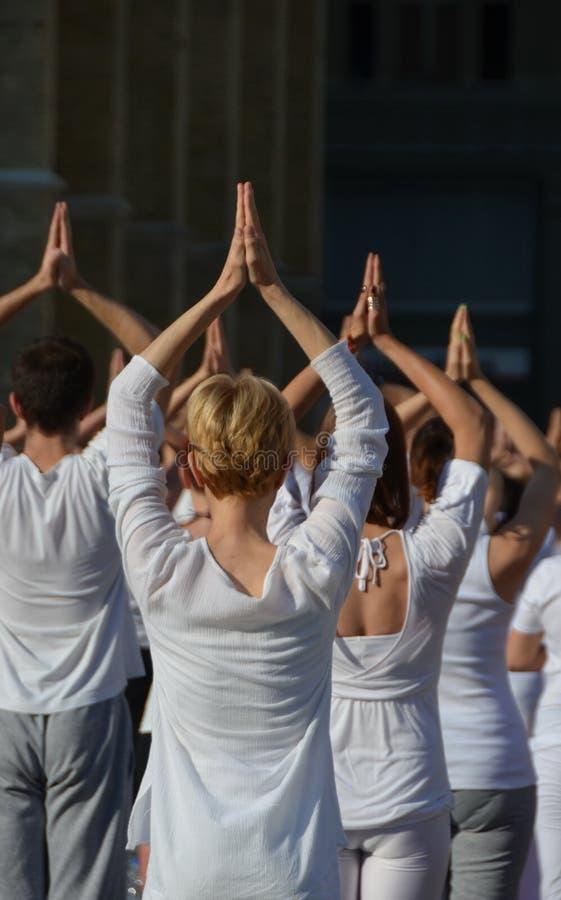 La gente participa en un acontecimiento de la yoga en el centro de la ciudad imagen de archivo libre de regalías