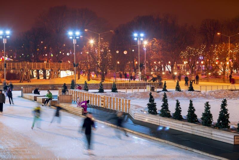La gente patina por la tarde en el parque en invierno fotografía de archivo libre de regalías