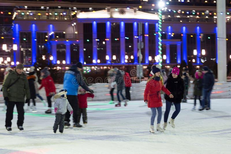 La gente patina por la tarde en una pista de patinaje de la ciudad imagenes de archivo