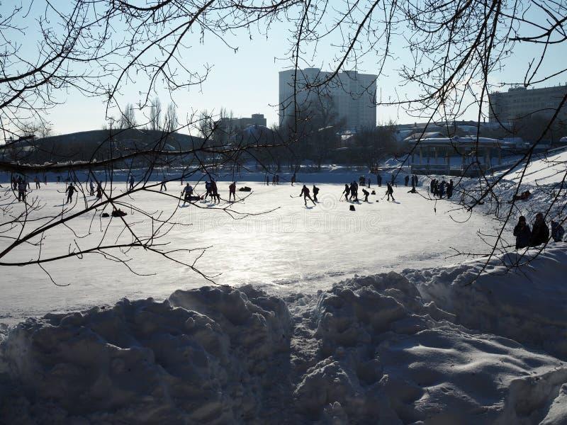 La gente pattina sulla pista di pattinaggio e gioca l'hockey un chiaro giorno gelido soleggiato fotografia stock libera da diritti