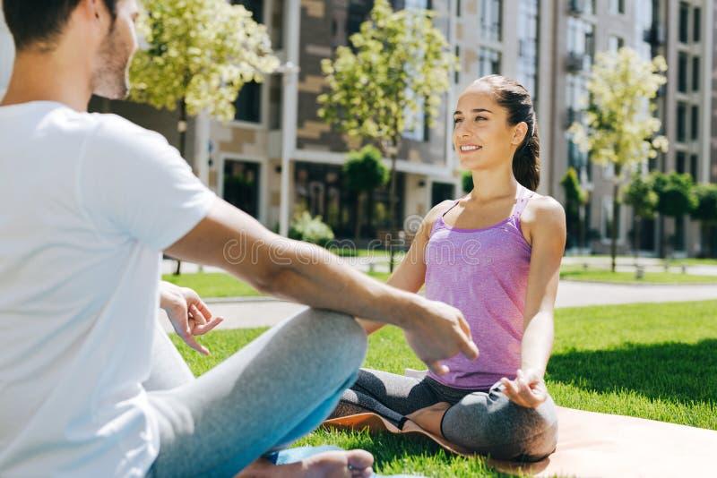 La gente piacevole contentissima che si siede nell'yoga posa immagine stock libera da diritti