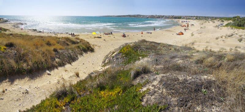 La gente prende il bagno del sole sulla spiaggia situata vicino alla città di Sampieri, Sicilia fotografia stock libera da diritti