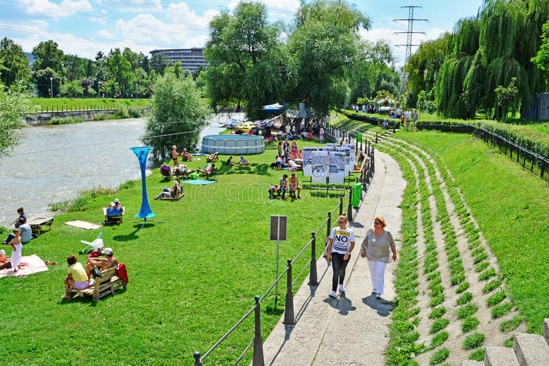 La gente prende un sunbath e socializza sulle sponde del fiume fotografia stock libera da diritti