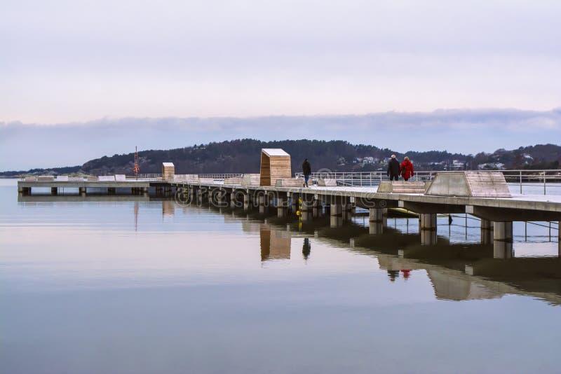 La gente que caminaba en un embarcadero largo reflejó en el agua, en un día de invierno tranquilo fotografía de archivo