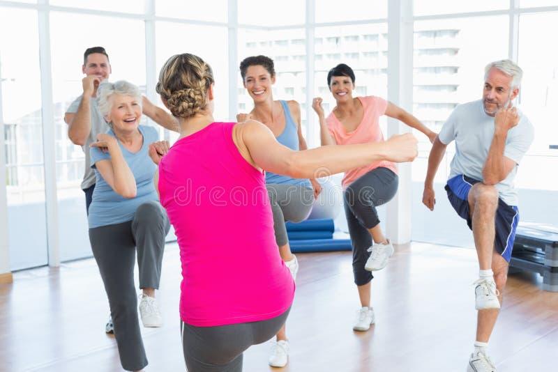 La gente que hace aptitud del poder ejercita en la clase de la yoga en estudio de la aptitud fotos de archivo libres de regalías