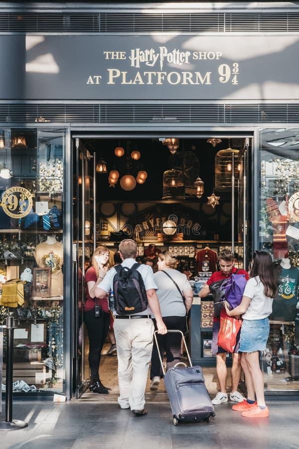 La gente que inscribe a Harry Potter hace compras por 9 3/4 plataforma dentro de la estación de la cruz del ` s del rey, Londres, foto de archivo libre de regalías