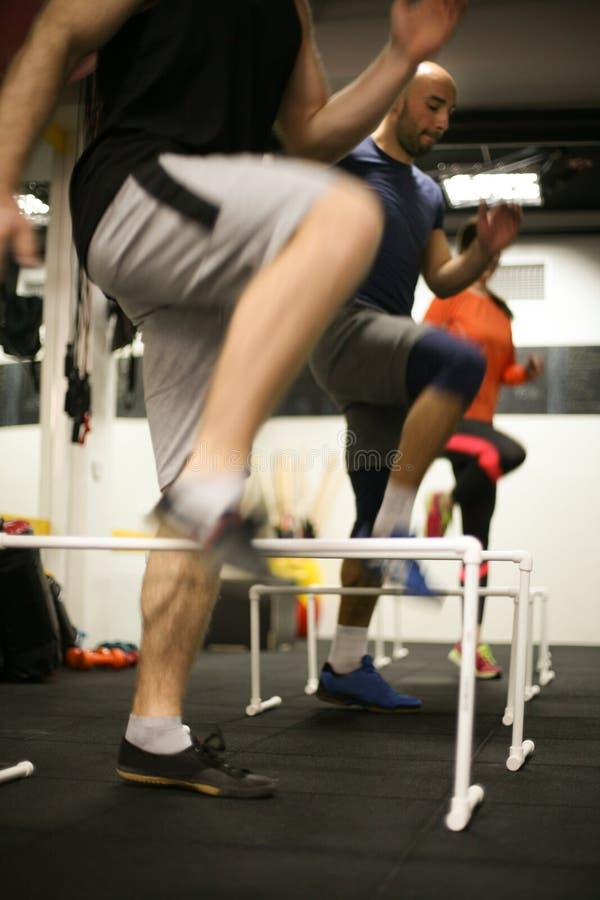 La gente que salta sobre obstáculos en gimnasio imagenes de archivo