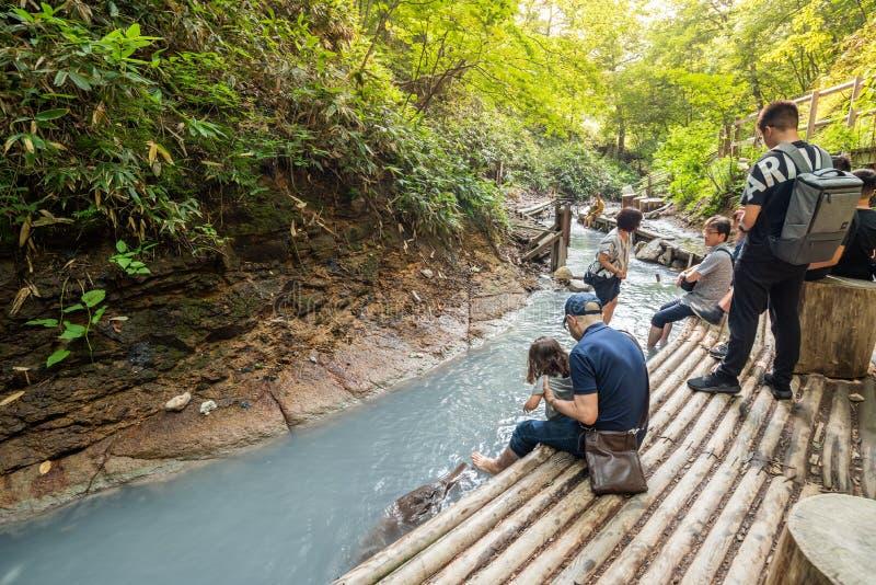 La gente que se relaja y que sumerge los dedos del pie en el gris onsen el río en Oyunuma Footbath natural fotos de archivo