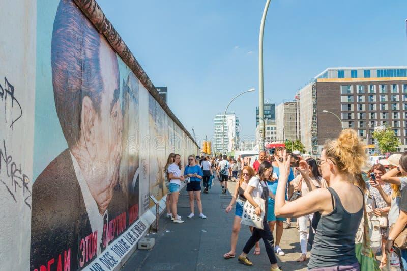 La gente que toma imágenes del muro de Berlín con la pintura de la pintada conocida como mi dios, me ayuda a sobrevivir este amor imagenes de archivo