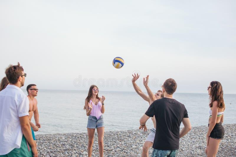 La gente raggruppa si diverte e gioca il beach volley al giorno di estate immagini stock libere da diritti