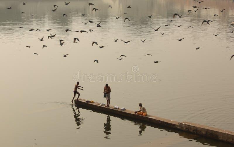 La gente recolecta para bañarse en el Ghats imagenes de archivo