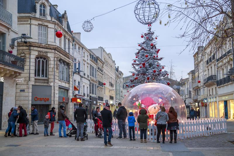 La gente recolectada cerca de una bola de cristal grande en una calle iluminó la decoración de la Navidad imagen de archivo libre de regalías