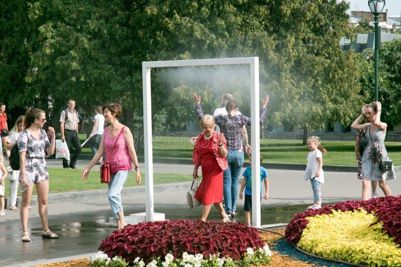 La gente se ahorra del calor del enfriamiento de la calle del calor de la niebla del agua en Europa ucrania kharkov 27 de julio,  imagenes de archivo