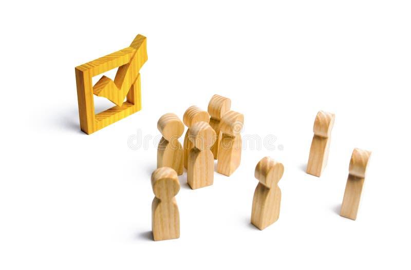 La gente se coloca cerca y mira la marca de verificación amarilla en la caja elección, encuesta, referéndum Los votantes particip fotos de archivo