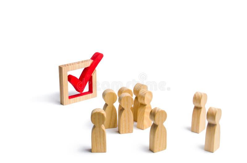 La gente se coloca cerca y mira la marca de verificación en la caja elección, encuesta o referéndum Los votantes participan en el imagenes de archivo