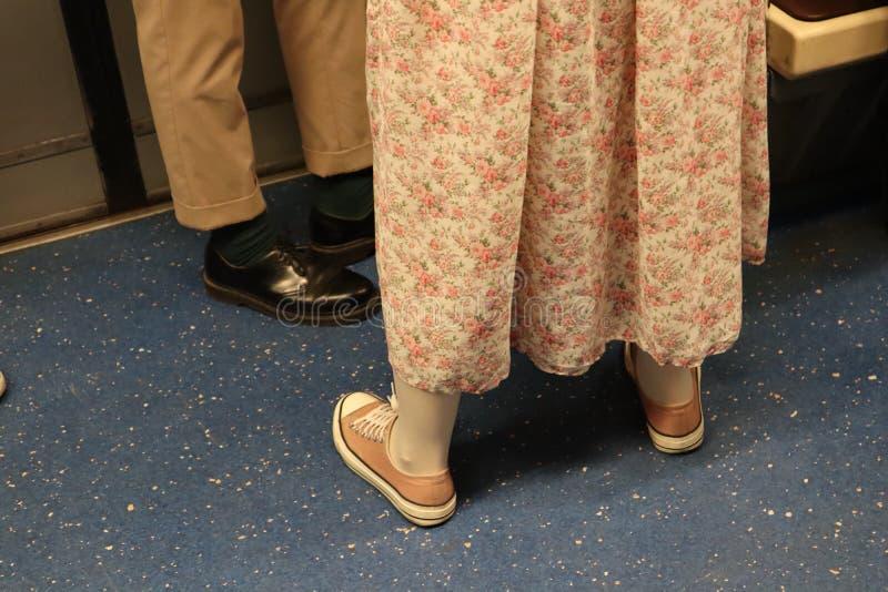La gente se coloca en el tren mire sus zapatos muchacha en un vestido rosado largo y zapatillas de deporte rosadas imagenes de archivo