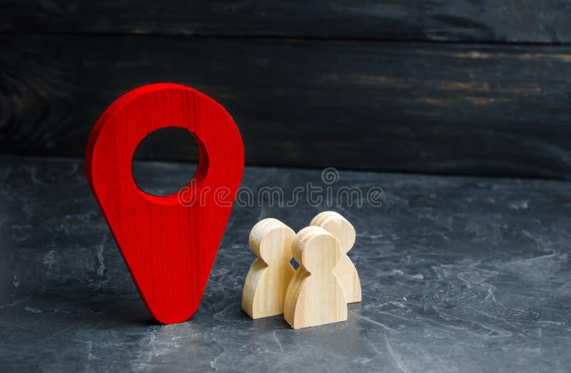 La gente se está colocando cerca del marcador de la ubicación Concepto de navegación y de lugar con el foco en los prismáticos Es fotografía de archivo libre de regalías
