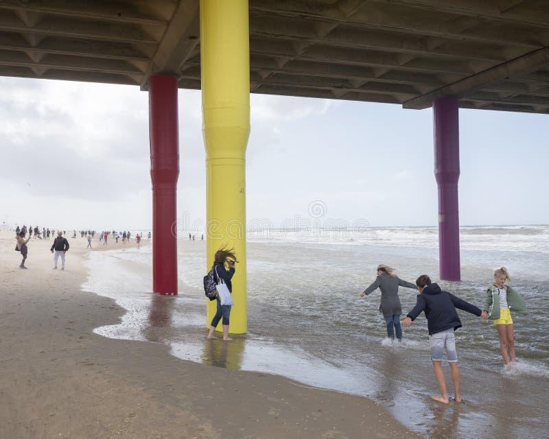 La gente se inclina en el viento debajo del embarcadero de Scheveningen en la playa de Mar del Norte en Holanda imagen de archivo