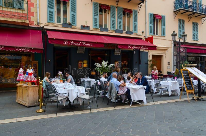 La gente se relaja en las tablas en el restaurante francés al aire libre Le Grand Balcon en la ciudad vieja, Niza, Francia foto de archivo libre de regalías