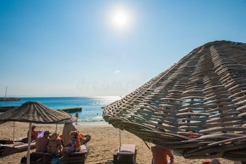 La gente se relaja en los ociosos del sol debajo de los paraguas por el mar fotos de archivo