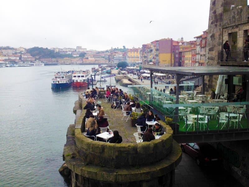 La gente se relaja en un café en la costa en el distrito histórico de Ribeira Oporto, Portugal fotos de archivo libres de regalías