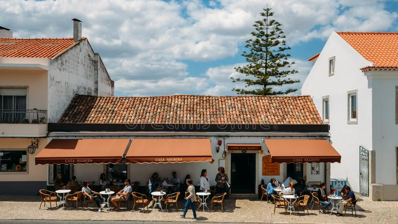 La gente se relaja en una terraza del café de Negrito de la casa en el pueblo encantador de Azeitao, de Portugal, de famosos por  fotografía de archivo