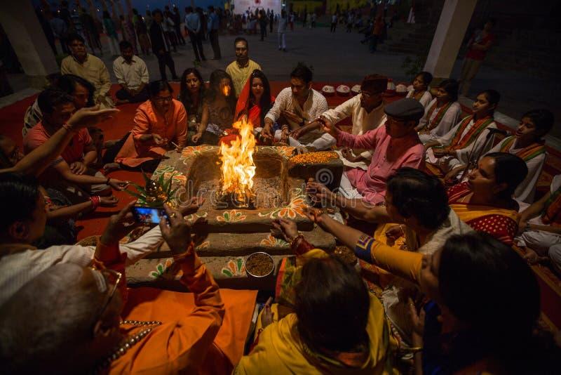 La gente se sienta cerca de un fuego ceremonial cerca del Ganges santo en la noche fotografía de archivo libre de regalías