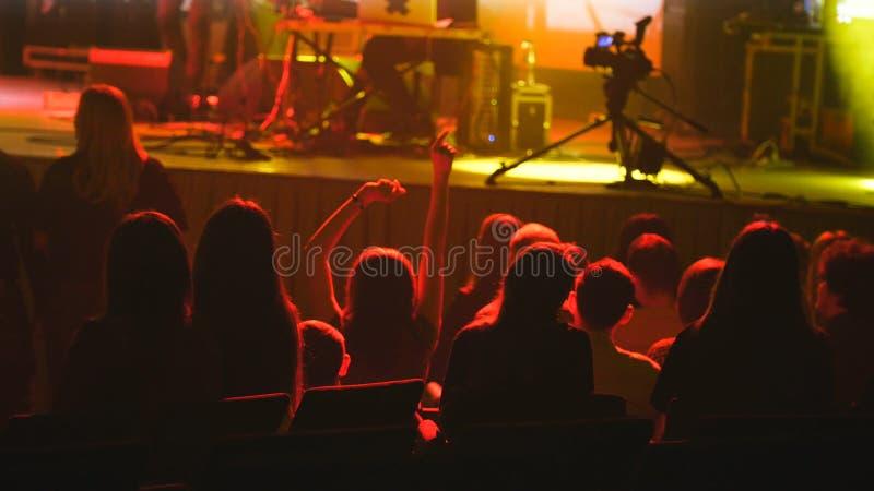 La gente se sienta en un concierto de rock - extracto borroso imagen de archivo libre de regalías