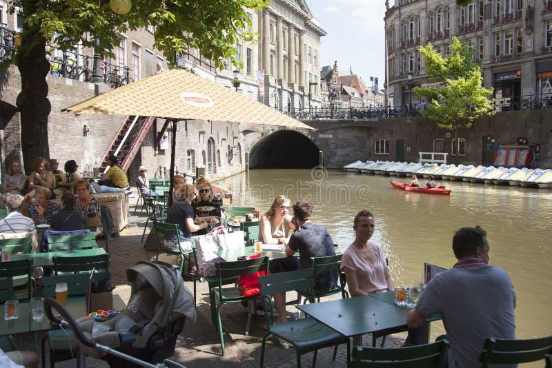 La gente se sienta y bebe en el café al aire libre en centro de ciudad de Utrecht medieval en Holanda fotografía de archivo libre de regalías