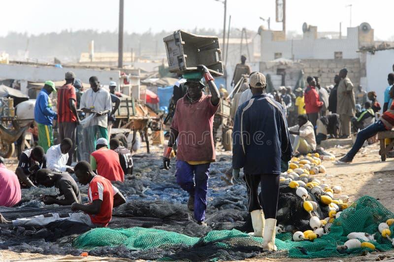 La gente senegalesa no identificada hace redes de pesca en la costa o foto de archivo