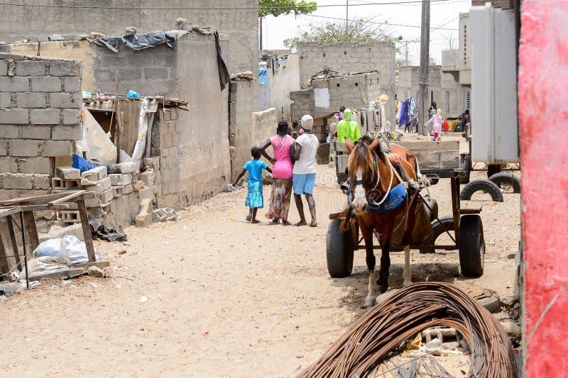 La gente senegalese non identificata cammina lungo la strada durante l'attività immagine stock
