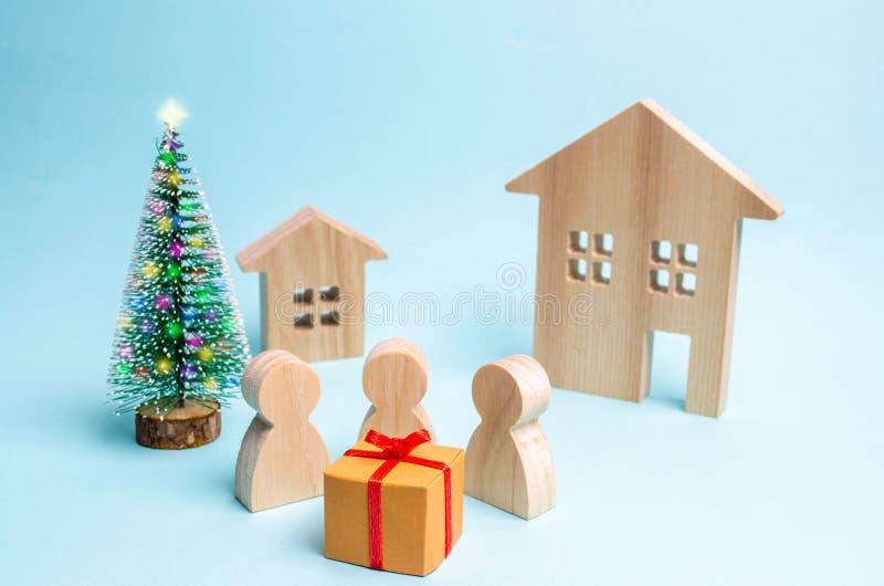 La gente si è riunita intorno al regalo ed è pronta ad aprirlo Vendita dei regali Vendita-fuori sorpresa Festa di Natale Festa de immagini stock